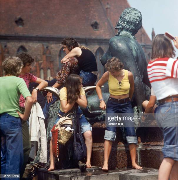 Passanten haben sich ihre Füße im Wasser des Neptunbrunnens vor dem Roten Rathaus in Berlin abgekühlt, im Hintergrund die Fassade der Marienkirche ,...