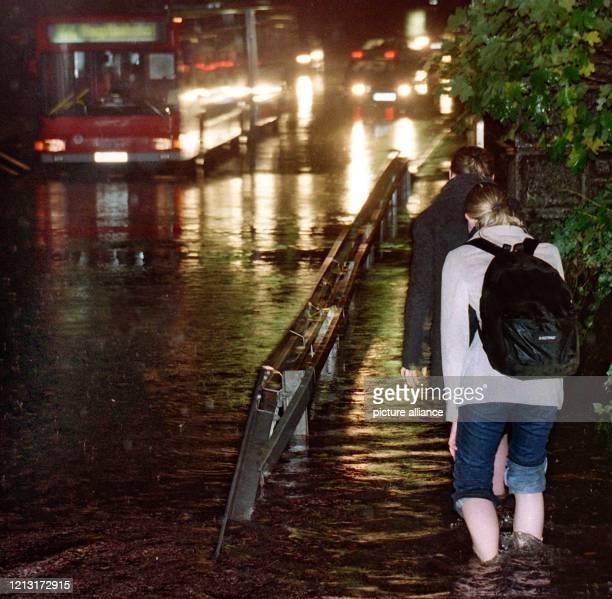 Passanten laufen am in Nürnberg auf dem Weg zur Arbeit mit hochgekrempelten Hosen barfuß durch die überfluteten Straßen während die Fahrzeuge...