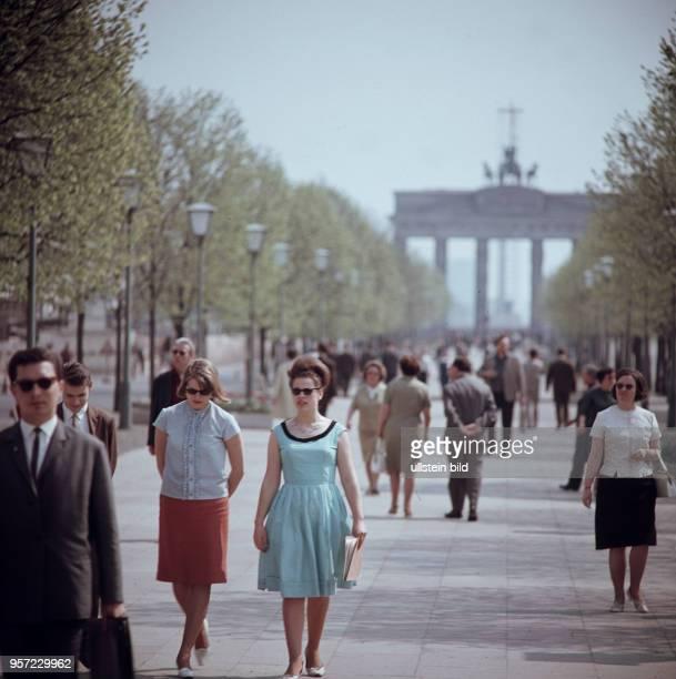 Passanten laufen auf dem Boulevard der Straße Unter den Linden in Berlin , im Hintergrund das Brandenburger Tor, aufgenommen im Frühjahr 1966.