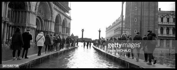 Passants marchant sur des passerelles lors d'inondations Venise Italie