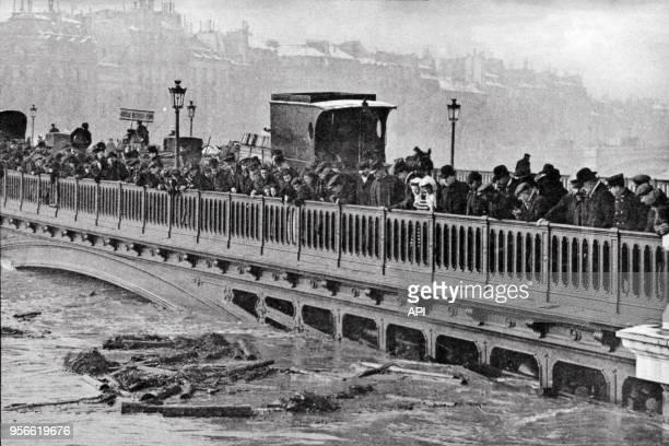 Passants observant la Seine en crue sur le Pont de Sully en 1910 à Paris France