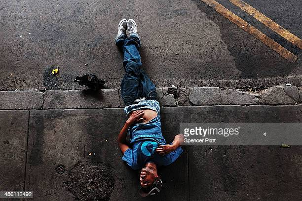 A passed out man lies on a sidewalk in an area which has witnessed an explosion in the use of K2 or 'Spice' a synthetic marijuana drug in East Harlem...