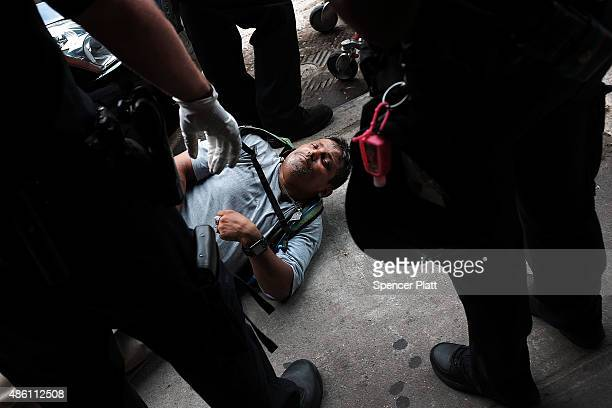 Passed out man lies on a sidewalk in an area which has witnessed an explosion in the use of K2 or 'Spice', a synthetic marijuana drug in East Harlem...