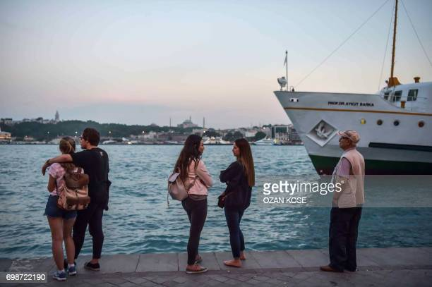 Passemgers wait near a ferry station in Karakoy District in Istanbul on June 20 as The Hagia Sophia Museum and Topkapi Palace are seen in the...