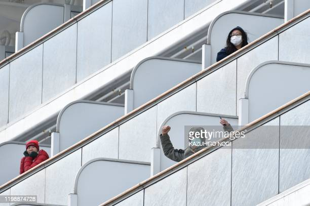 TOPSHOT A passenger aboard the Diamond Princess cruise ship waves to the media upon arriving at Yokohama port on February 6 2020 Ten more people on a...