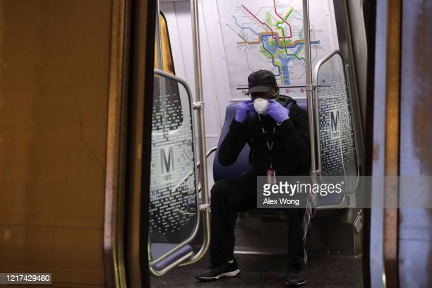 A passenger adjusts his mask in a Metro train car at Metro Center Station April 7 2020 in Washington DC Washington Metropolitan Area Transit...