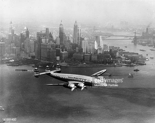 A TWA passenger aircraft flying amid the skyscrapers New York 1950s