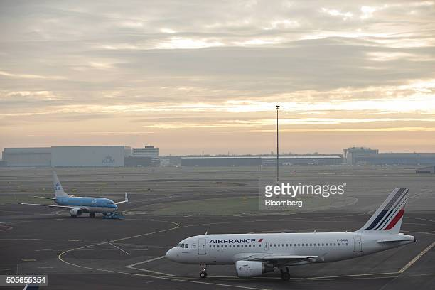 Passenger aircraft operated by Air FranceKLM Group right and a KLM jet sit on the tarmac at Schiphol Airport operated by the Schiphol Group in...