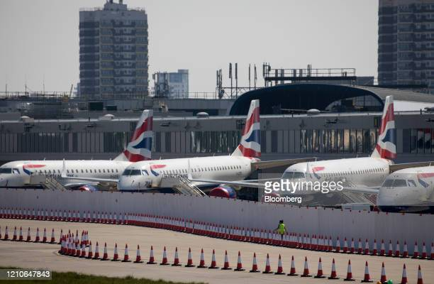 Passenger aircraft, operated by British Airways, a unit of International Consolidated Airlines Group SA , sit with their engines covered behind a...
