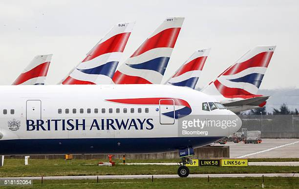 A passenger aircraft operated by British Airways a unit of International Consolidated Airlines Group SA taxis past the tail fins of other British...