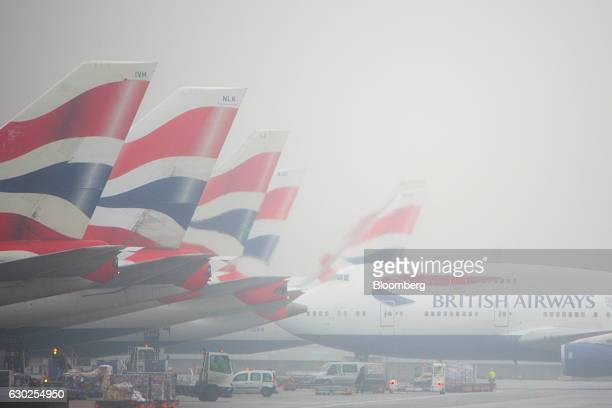 A passenger aircraft operated by British Airways a unit of International Consolidated Airlines Group SA pulls into a gate in fog at Terminal 5 at...