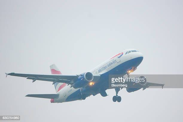 A passenger aircraft operated by British Airways a unit of International Consolidated Airlines Group SA takes off in fog from Terminal 5 at London...
