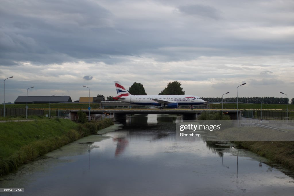 A passenger aircraft, operated by British Airways, a unit of International Consolidated Airlines Group SA (IAG), crosses a bridge after landing at Schiphol airport in Amsterdam, Netherlands, on Tuesday, Aug. 15, 2017. Delta Air Lines Inc., China Eastern Airlines Corp. and Air France-KLM Group are reaching for their checkbooks to forge a deeper global alliance. Photographer: Jasper Juinen/Bloomberg via Getty Images