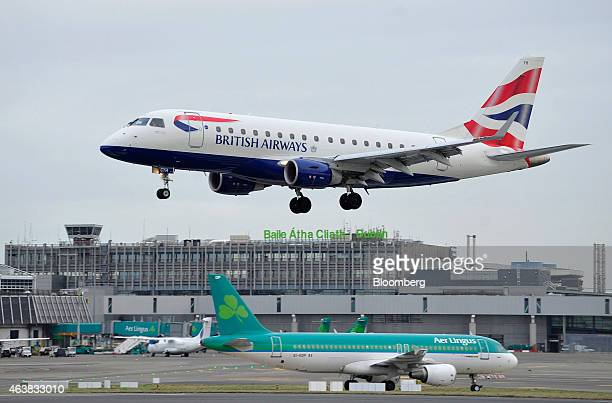 A passenger aircraft operated by British Airways a unit of IAG SA passes above an Airbus A320 passenger aircraft operated by Aer Lingus Group Plc as...