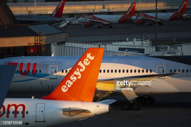 Passenger aircraft, operated by Easyjet Plc and Tui AG, stand grounded on the tarmac at Manchester Airport, operated by Manchester Airport Plc, in...