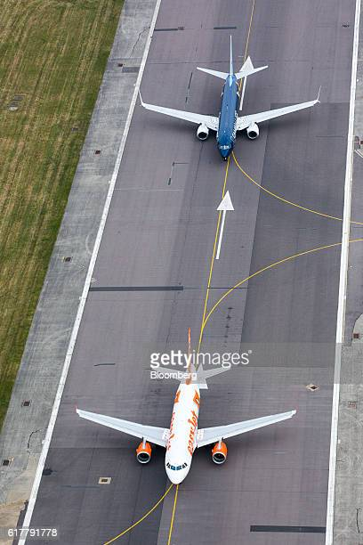 Passenger aircraft, operated by Easyjet Plc, bottom, and TUI AG, top, queue for take off from at London Gatwick airport in this aerial view taken...
