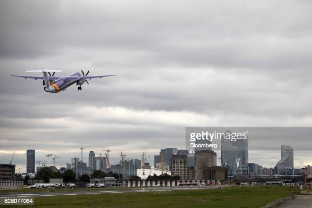 A passenger aircraft operated by Flybe Group Plc takes off towards the Canary Wharf financial business and shopping district at London City Airport...