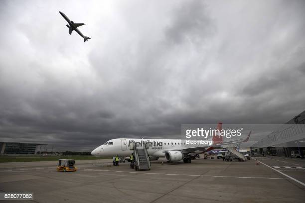 A passenger aircraft operated by Helvetic Airways AG sits on the tarmac as an aircraft operated by British Airways a unit of International...