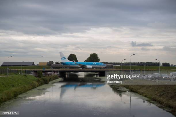 A passenger aircraft operated by KLM the Dutch arm of Air FranceKLM Group crosses a bridge after landing at Schiphol airport in Amsterdam Netherlands...
