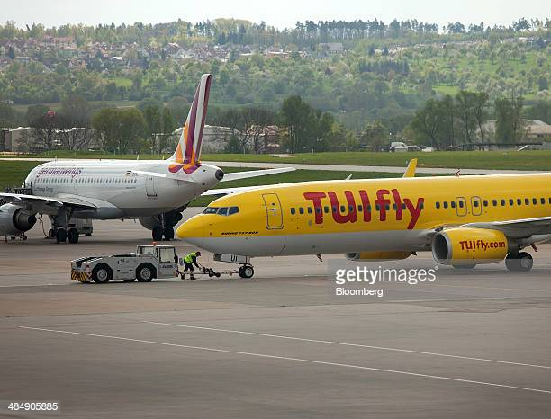 A passenger aircraft operated by lowcost airline TUI Fly sits connected to a tow tractor as a Germanwings aircraft a lowcost subsidiary of Deutsche...