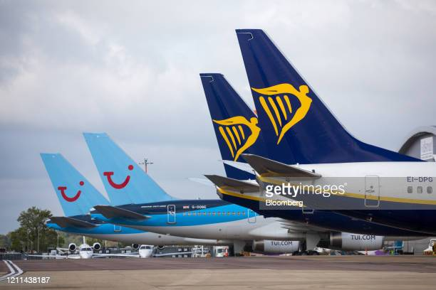 Passenger aircraft, operated by Ryanair Holdings Plc, right, stand near passenger aircraft, operated by Tui AG, at London Luton Airport in Luton,...