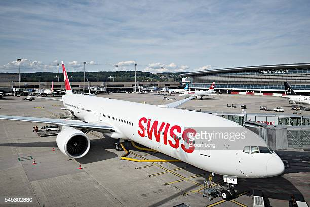 A passenger aircraft operated by Swiss International Air Lines AG sits parked at a gate at Zurich Airport operated by Flughafen Zuerich AG in Zurich...