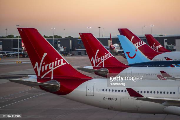 Passenger aircraft, operated by Tui AG and Virgin Atlantic Airways Ltd., sit grounded on the tarmac at Manchester Airport, operated by Manchester...