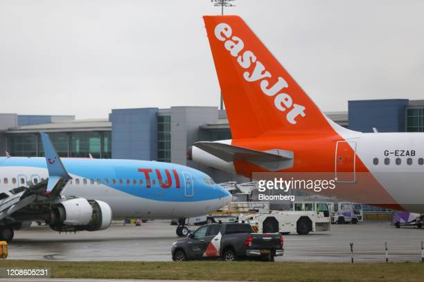 Passenger aircraft, operated by Tui AG, sits parked near a grounded passenger aircraft operated by Easyjet Plc, at London Luton Airport in Luton,...