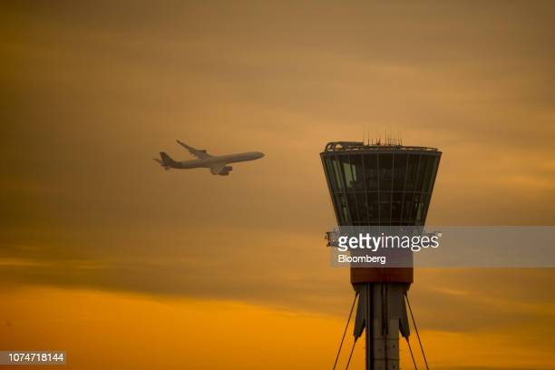 A passenger aircraft operated by Virgin Atlantic Airways Ltd flies past a control tower at London Heathrow Airport in London UK on Monday Dec 24 2018...