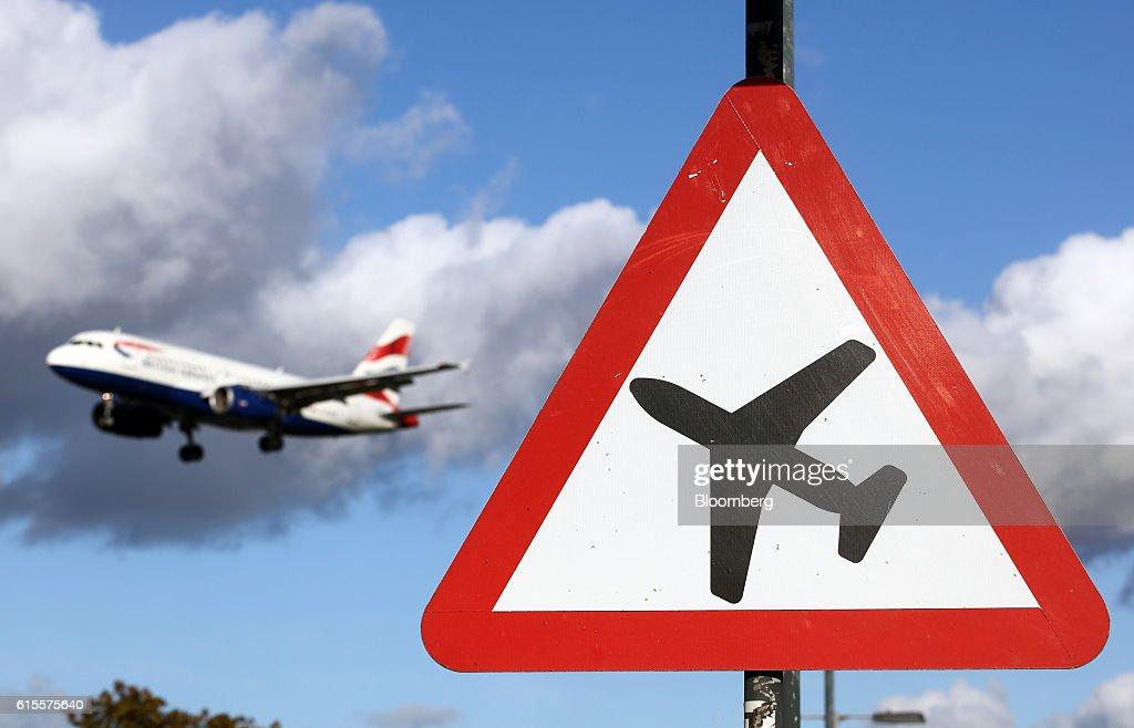 A passenger aircraft passes a airplane warning sign as it