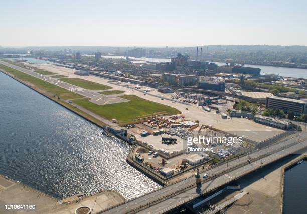 Passenger aircraft sit on the tarmac behind a newly-built temporary hoarding at the closed London City Airport, operated by London City Airport Ltd....