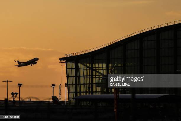 A passenger aircraft takes off alongside Terminal 5 during sunrise at London Heathrow Airport in west London on October 17 2016 Britain's government...
