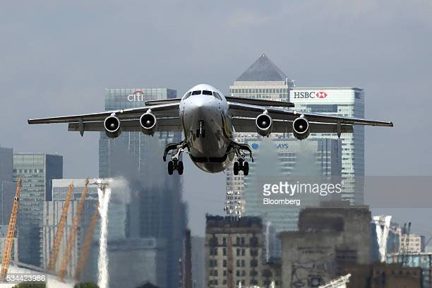 A passenger aircraft takes off from London City Airport against a backdrop of Canary Wharf business financial and shopping district in London UK on...