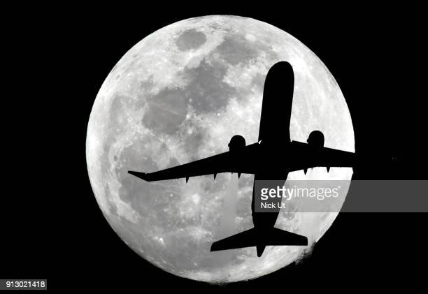 A passenger airliner makes its path across the the moon before becoming a socalled 'super blue blood moon' January 31 2018 seen from Whittier...