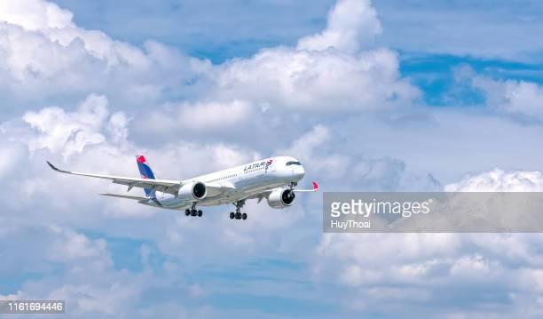 passagierflugzeug airbus a350 von latam airlines fliegt über stadt und bereitet sich auf landung vor - flugzeugheck stock-fotos und bilder
