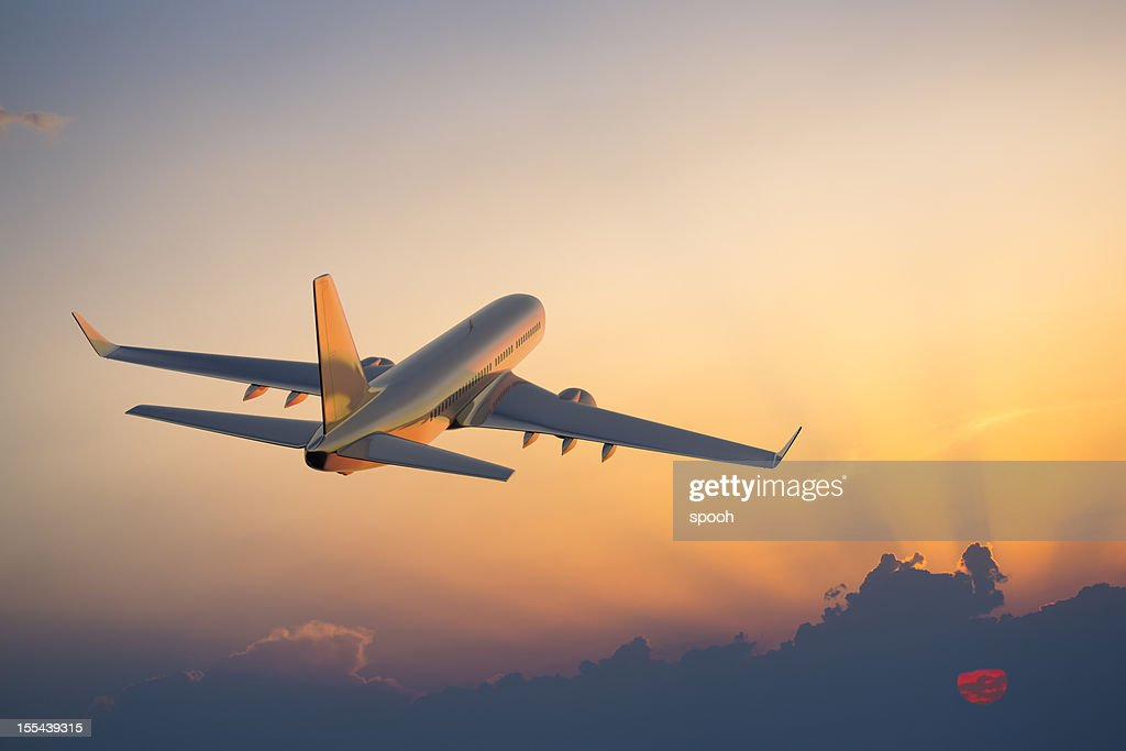 Passenger airplane flying above clouds during sunset : Stock Photo