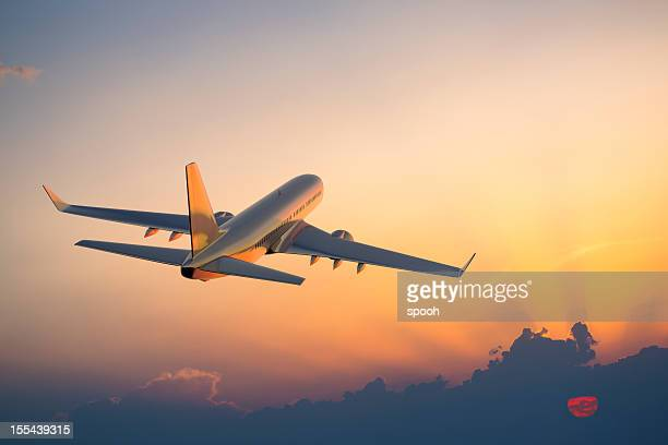 Passenger airplane flying above clouds during sunset