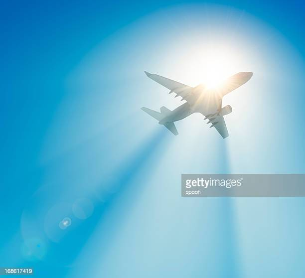 Passenger airplane flying against the sun