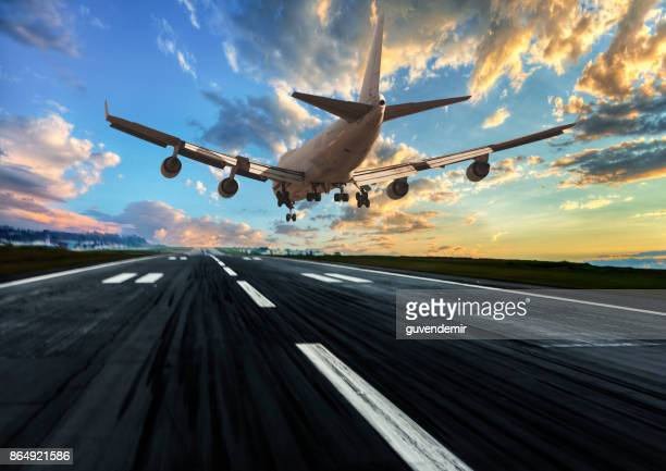 passenger airplane landing at dusk - landing gear stock photos and pictures