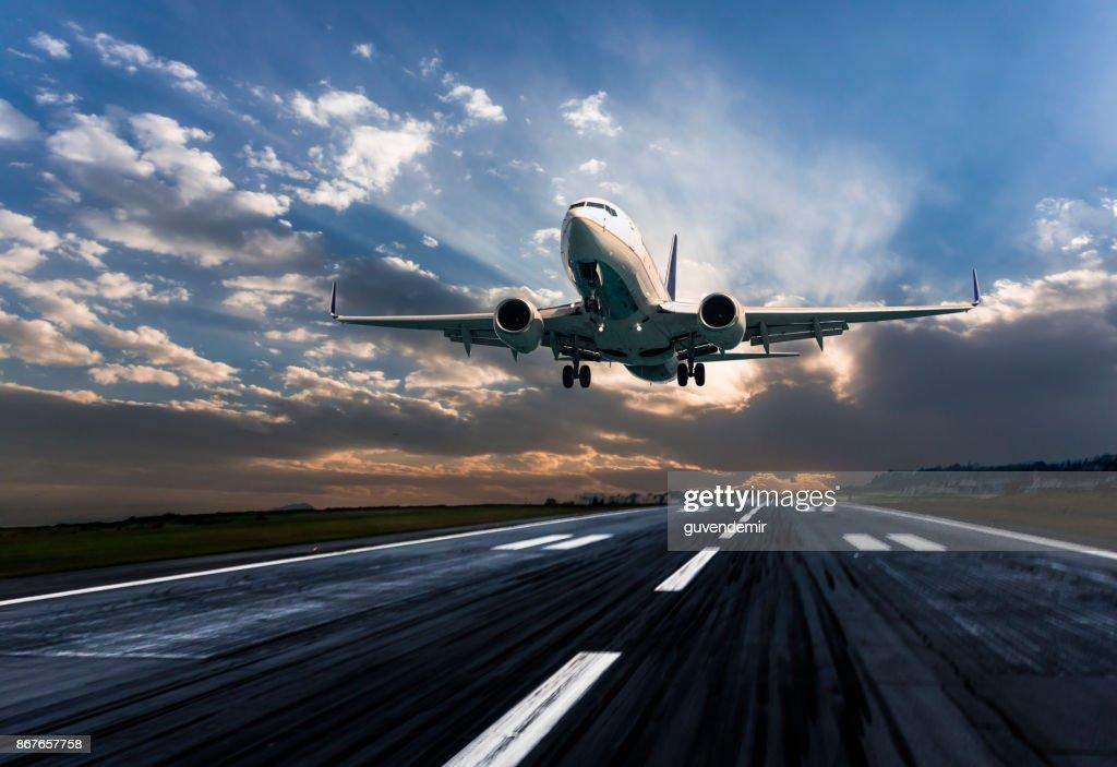 Passenger airplane landing at dusk : Stock Photo