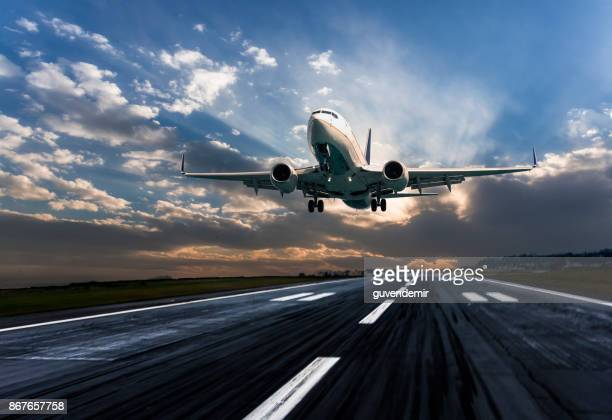 passenger airplane landing at dusk - aeroplane stock photos and pictures
