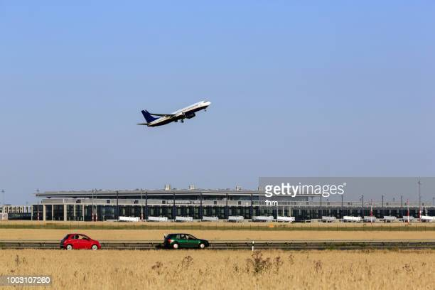 a passenger airplane takes off in berlin-schönefeld airport with new terminal building in the background (brandenburg, germany) - airfield stock pictures, royalty-free photos & images