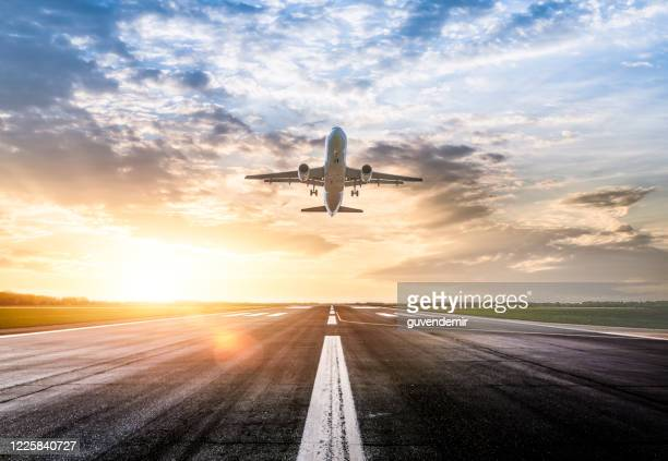 passenger airplane taking of at sunrise - aeroplane stock pictures, royalty-free photos & images