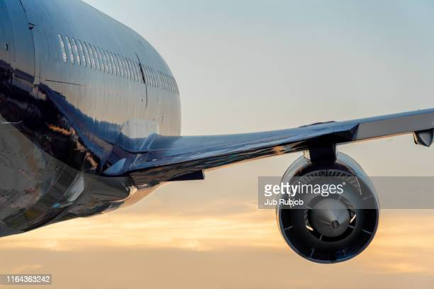 passenger airplane taking off at sunset - airplane stock pictures, royalty-free photos & images