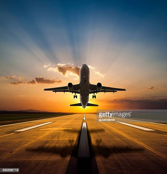 passenger airplane taking off at sunset - aircraft stock photos and pictures