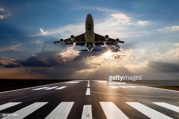 passenger airplane taking off at sunset - aeroplane stock pictures, royalty-free photos & images