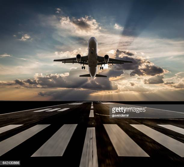 Passenger airplane taking off at sunset