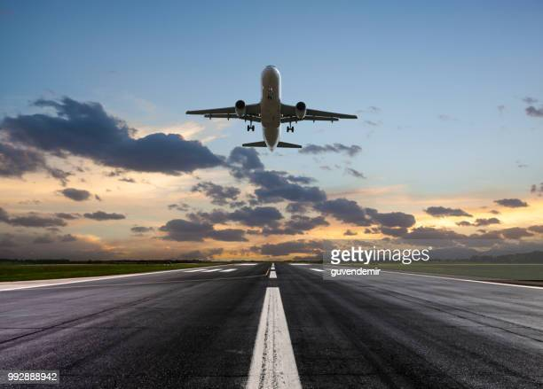 passenger airplane taking off at sunset - airport runway stock pictures, royalty-free photos & images