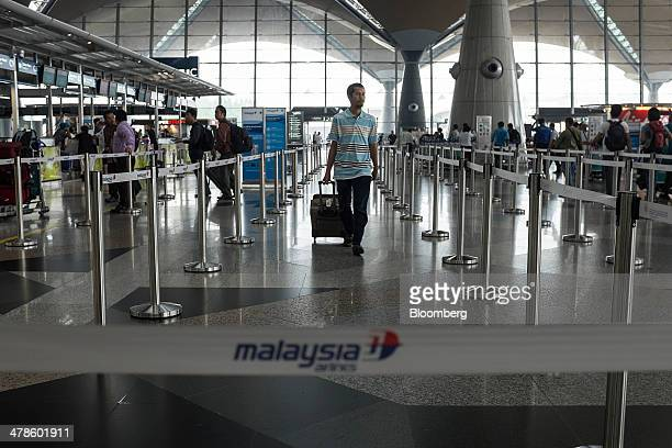 A passenger arrives at the checkin area for Malaysian Airline System Bhd at Kuala Lumpur International Airport in Sepang Malaysia on Friday March 14...
