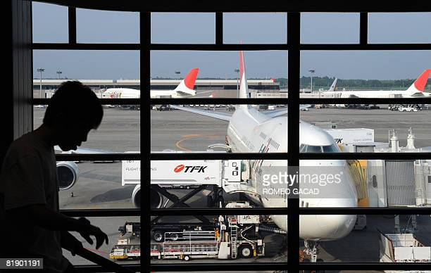 Passenger arrives at the departure lounge for Japan Airlines at Narita airport in Tokyo on July 10, 2008. Blaming the decision on soaring oil price,...